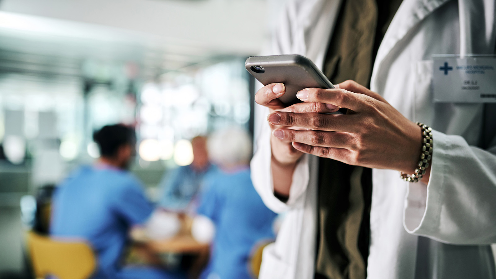 Cropped shot of an unrecognizable female doctor using a smartphone in a hospital with her colleagues in the background