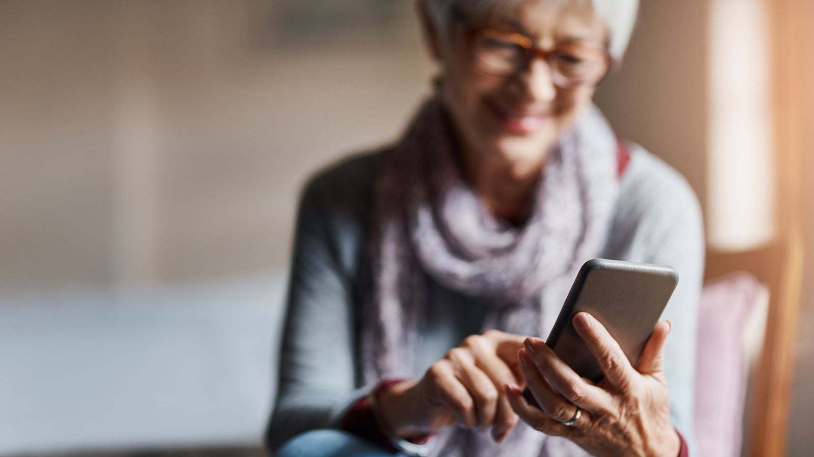 Shot of a senior woman using a mobile phone in a retirement home
