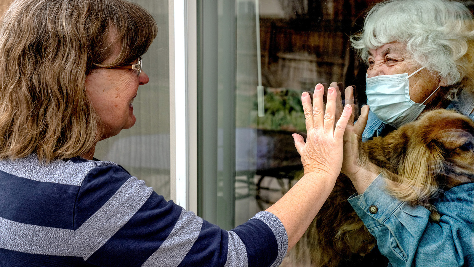 A touching moment as a mother visits with her daughter at the window of her home because of having COVID 19
