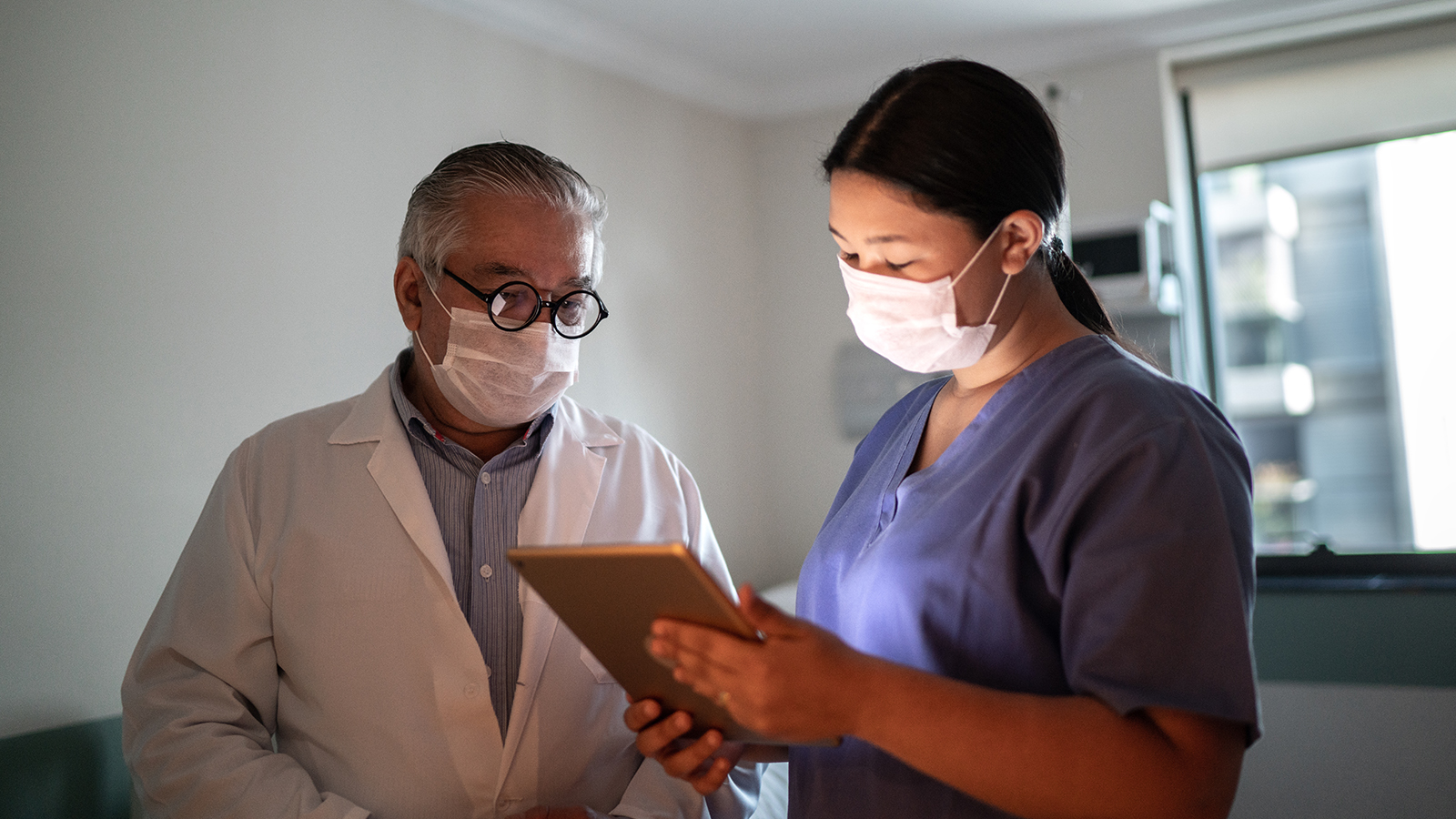 Healthcare workers talking and using digital tablet with face mask in hospital
