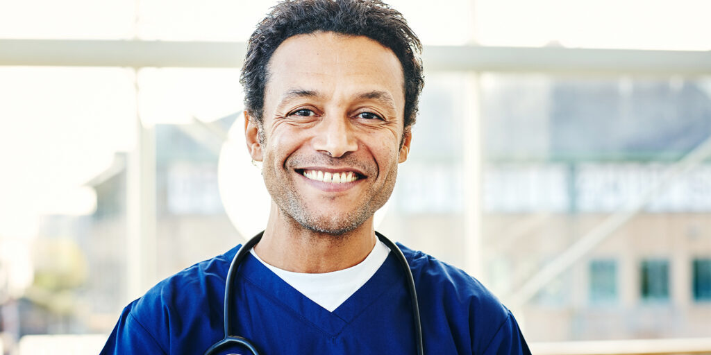 Portrait of successful male surgeon with stethoscope around his neck and smiling in hospital