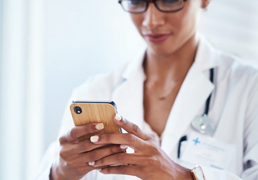 Shot of a young doctor using a smartphone in her consulting room