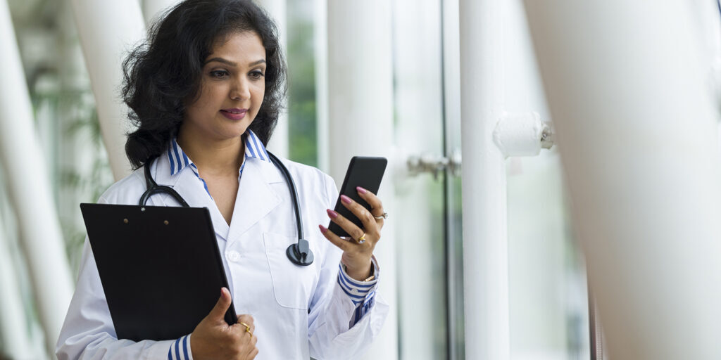Attractive Asian health care professional reading text messages on a smart phone. Shot with telephone lens using shallow depth of field to blur out background details.